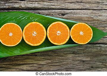 Orange fruit Slices on leaf and wooden background, nature...