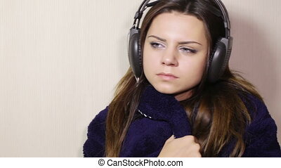 Girl in bathrobe with headphones - Seated in the headphones...