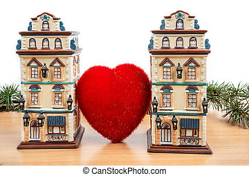 two buildings between big heart on wooden table with white...
