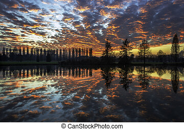 Winter sunset in the shore of a lake with clouds reflected...