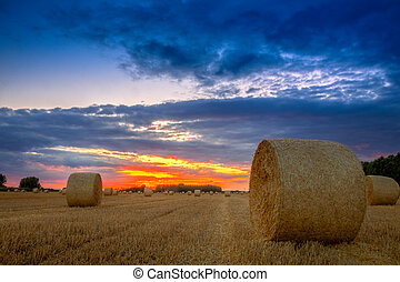 End of day over field with hay bale in Hungary. This photo...