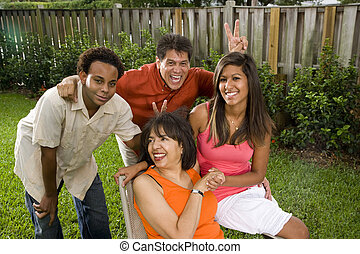 Interracial family relaxing in back yard - Interracial...