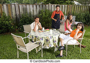 Interracial family having back yard barbecue