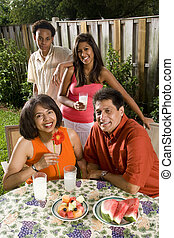 Interracial family in backyard having refreshments