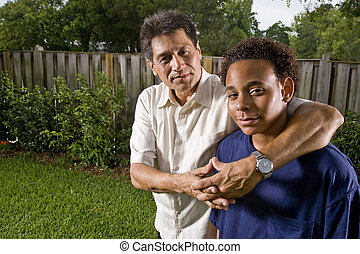 Teenage boy with proud father - Interracial family, portrait...