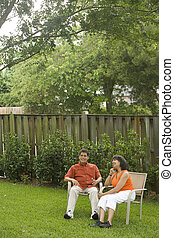 Mature interracial couple relaxing in back yard