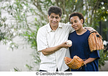 Hispanic father with African American teenage son holding...