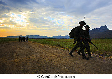 silhouette motion of long range patrolling soldier walking...