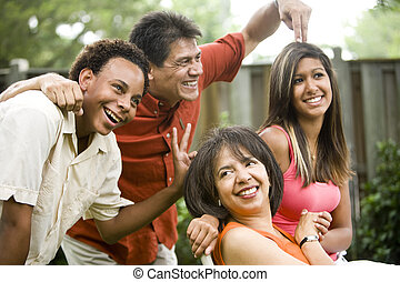 Interracial family making silly gestures posing for photograph