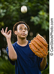 Teenage boy tossing a baseball up in the air - African...