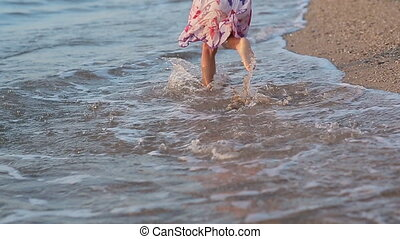 Little girl runing along the beach in sundress in slow...