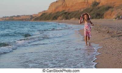 Little girl running along the beach leaving footprints in the sand in slow motion