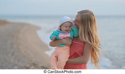 Young mother holding baby in her arms while standing near the sea in slow motion