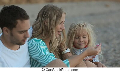 Close up of young parents with little daughter looking at stones while sitting near the sea