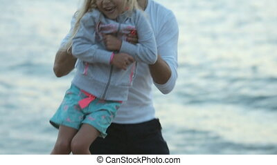 Happy family at the seashore, father and daughter having fun