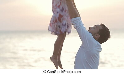 Father throws daughter into the air near the sea at sunset in slow motion