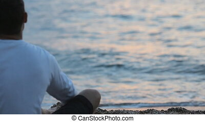 Man sitting near the sea and throwing stones into the water...
