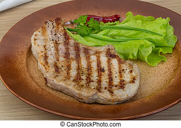 Grilled t-bone steak with salad leaves and parsley