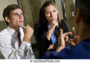 Two young businesspeople listening to colleague