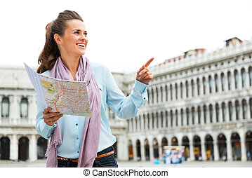 Happy young woman with map pointing on piazza san marco in...