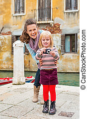 Happy mother and baby girl taking photo in venice, italy