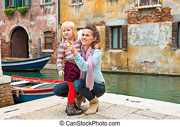 Baby girl and mother poiting on copy space while in venice,...