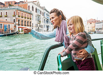Baby girl and mother poiting while travel by vaporetto in...