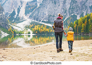 Mother and baby walking on lake braies in south tyrol,...