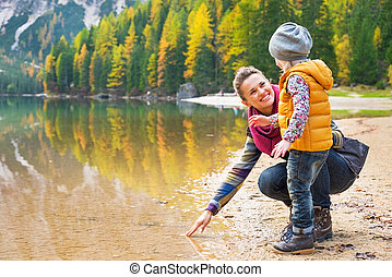 Mother and baby playing with water on lake braies in south...