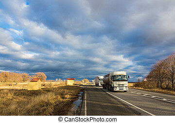 Trucks moving by the road under a beautiful autumn cloudy...