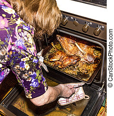 woman cuts roasted goose with a knife