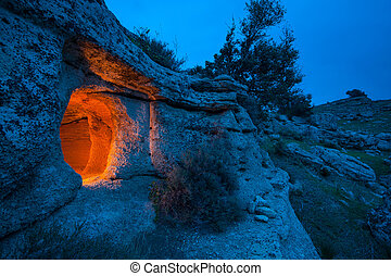 Pantalica at dusk - View of a rock-cut tomb in the rocky...