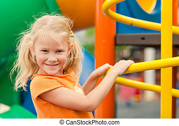 Happy little girl on the playground at the day time