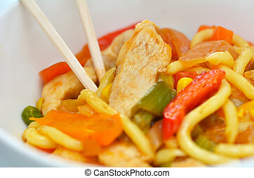 Asian noodles dish of chicken and vegetables served in a...