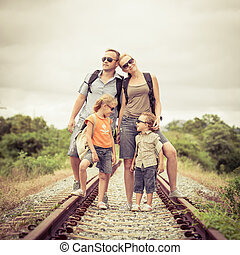 Happy family walking on the railway at the day time. Concept...
