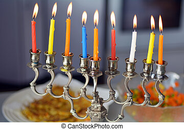 Hanukkah menorah lit with eight candles during dinner...
