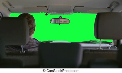 Man drives a car. Green background - The driver makes a...