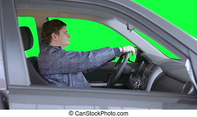 Man drives a car. Green background - The driver looks...