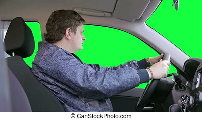 Man drives a car. Green background - The driver looks up....