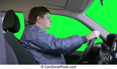 Man drives a car Green background - The driver looks around...