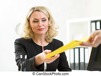middle-aged businesswoman giving paper to colleague - mature...