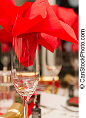 Christmas party table with red napkin in a glass