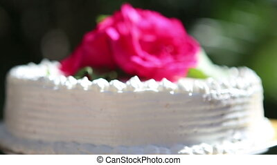 white creamy delicious cake - three red roses on the top of...