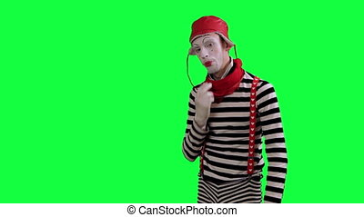 The mime feels stuffy and hot - The boy mime against a green...