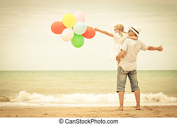 Father and daughter with balloons playing on the beach at...