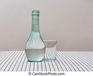 Rustic green carafe of water with drinking glass -...