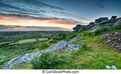 Moorland Sunset - Sunset over a granite tor on moorland in...
