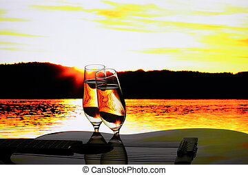 Two champagne glasses with guitar at sunset, close up