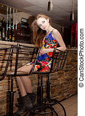 Beautiful young girl with her hair down at the bar in the...