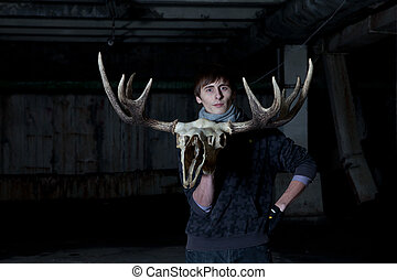 young man with a deer skull with horns in hand in a dark...
